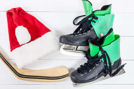 Overhead view of hockey ice skates accessories placed on white wooden table. Items included hockey stick, ice skates and santa hat. Winter sport leisure time concept.