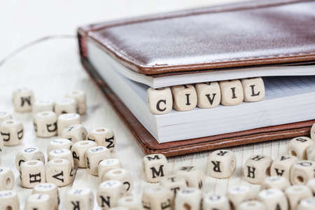 seizing: Word Civil written on a wooden block in a book. On old white wooden table.