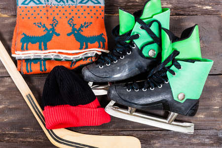 Overhead view of hockey ice skates accessories placed on old rustic wooden table. Items included hockey stick, ice skates, scarf and hat. Winter sport leisure time concept.