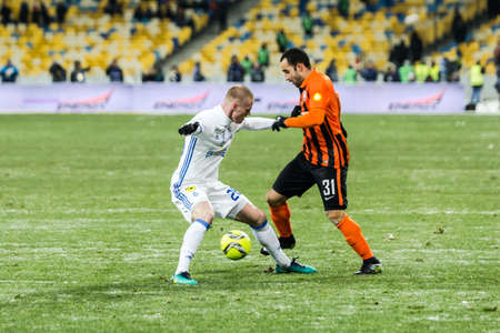 olimpiyskiy: Kiev, Ukraine - December 12, 2016: Mykyta Burda of Dynamo Kyiv fighting for the ball with Ismaili of Shakhtar during Ukrainian Premier League match at NSC Olimpiyskiy stadium.
