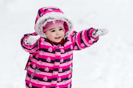 Portrait of little girl in pink jacket with red scarf and pink hat in snowy park at winter.