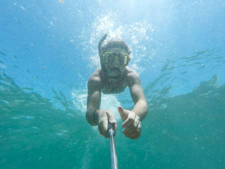Underwater selfie shot with selfie stick. Deep blue sea. Wide angle shot.