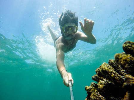 Selfie subacqueo girato con bastone selfie. Profondo mare blu. Colpo grandangolare.
