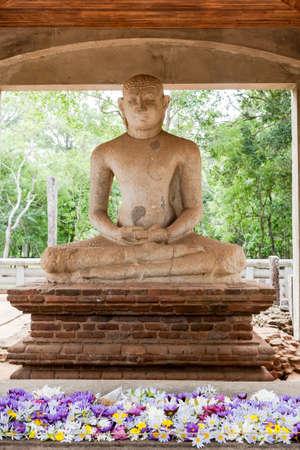 The meditating Samadhi Buddha Statue with the colorful lotus flowers on the altar, Anuradhapura, Sri Lanka. Stock Photo
