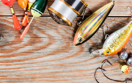 View of fishing accessories on white wooden table. Items include fishing reel, wobblers, floats and dock. Stock Photo