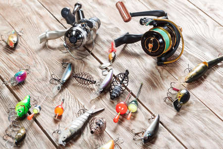 intend: View of fishing accessories on white wooden table. Items include fishing reel, wobblers, floats and dock. Stock Photo