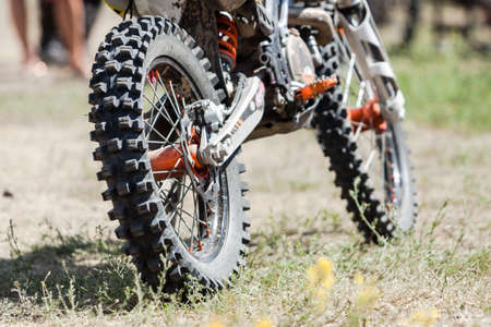 Close-up of muddy rear wheel and engine of dirt motorcycle details. Extreme sport competition.