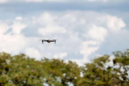 Létající drone s modrou oblohou pod kontrolou profesionálního fotografa