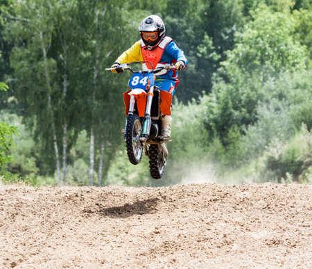 thru: Kiev, Ukraine - July 16, 2017: Kid on motorcycle going thru dirt, during Championship of Ukraine on cross-country final stage.