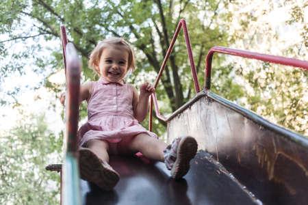 Active little girl having fun on a children playground.