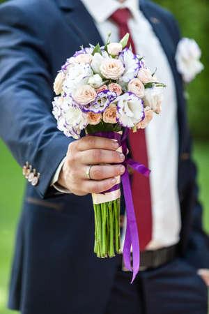 Stylish elegant happy groom with bouquet, wedding, mans fashion