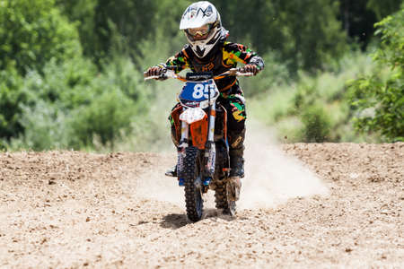 Kiev, Ukraine - July 16, 2017: Kid on motorcycle going thru dirt, during Championship of Ukraine on cross-country final stage.