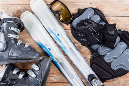 Overhead view of ski and snowboard accessories placed on rustic wooden table. Items included boots, goggles, gloves, ski and back protection. Winter sport leisure time concept.