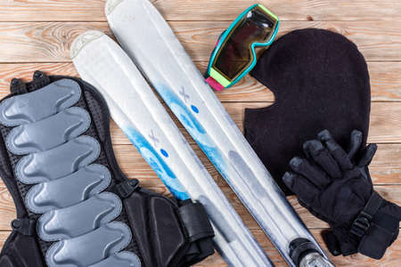 Overhead view of ski and snowboard accessories placed on rustic wooden table. Items included mask, goggles, gloves, ski and back protection. Winter sport leisure time concept.