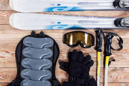 Overhead view of ski and snowboard accessories placed on rustic wooden table. Items included sticks, goggles, gloves, ski and back protection. Winter sport leisure time concept.