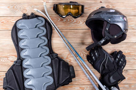 Overhead view of ski and snowboard accessories placed on rustic wooden table. Items included helmet, goggles, gloves, ski and back protection. Winter sport leisure time concept. Reklamní fotografie