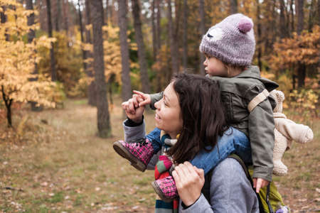 Little girl in autumn forest with teddy bear backpack sitting on mother shoulders. Fall day. Little girl exploring nature with mother.