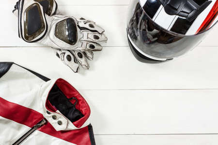 Overhead view of biker accessories placed on white wooden table. Items included motorcycle helmet, gloves and jacket. Motorcycle travel dream concept. Reklamní fotografie