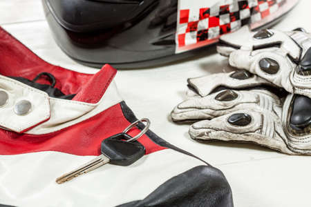 View of motorcycle rider accessories. Items included motorcycle helmet, gloves, keys and jacket. Motorcycle travel dream concept.