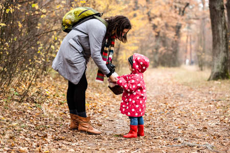Little girl and mother in autumn forest with basket. Fall day. Little girl exploring nature with mother. Reklamní fotografie
