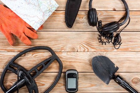Overhead view of metal detector accessories placed on rustic wooden table. Items included metal detector, shovel, knife, gps, gloves, map and headphones. Treasure hunters concept.