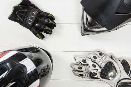 Overhead view of biker accessories placed on white wooden table. Items included motorcycle helmet and gloves. Motorcycle travel dream concept.