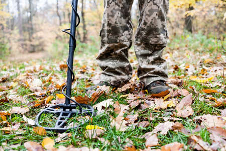 Man with electronic metal detector device working on outdoors background. Close-up photography of searching process.