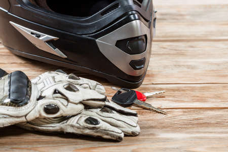 Overhead view of biker accessories placed on rustic wooden table. Items included motorcycle helmet, gloves and keys. Motorcycle travel dream concept. Reklamní fotografie