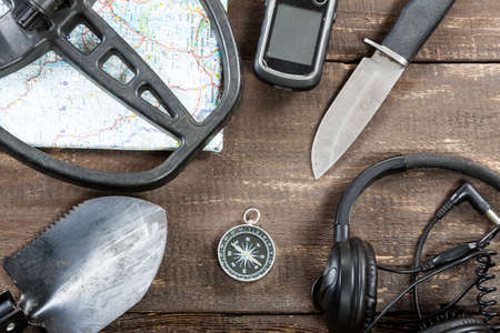 Overhead view of metal detector accessories placed on rustic wooden table. Items included metal detector, shovel, knife, gps, map, compass and headphones. Treasure hunters concept. Reklamní fotografie
