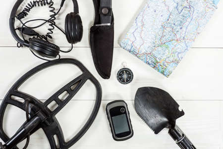 Overhead view of metal detector accessories placed on white wooden table. Items included metal detector, shovel, knife, gps, compass, map and headphones. Treasure hunters concept. Reklamní fotografie