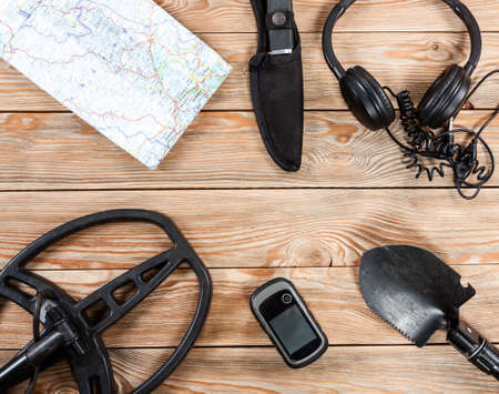 Overhead view of metal detector accessories placed on rustic wooden table. Items included metal detector, shovel, knife, gps, map and headphones. Treasure hunters concept.