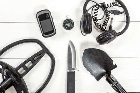 Overhead view of metal detector accessories placed on white wooden table. Items included metal detector, shovel, knife, gps, compass and headphones. Treasure hunters concept. Reklamní fotografie