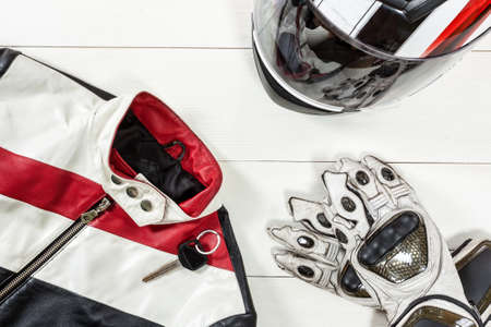 Overhead view of biker accessories placed on white wooden table. Items included motorcycle helmet, gloves, keys and jacket. Motorcycle travel dream concept.