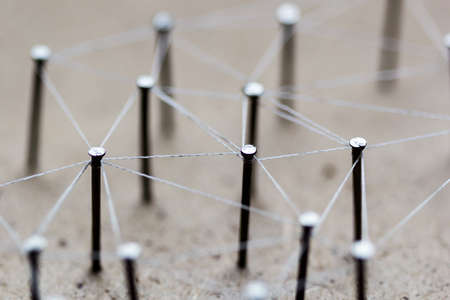 Linking entities. Network, networking, social media, connectivity, internet communication abstract. A small network connected to a larger network. Web of threads on cork board. Stock Photo