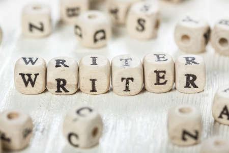 Word Writer vytvořený dřevěnými abecedními bloky. Na starém dřevěném stole. Reklamní fotografie
