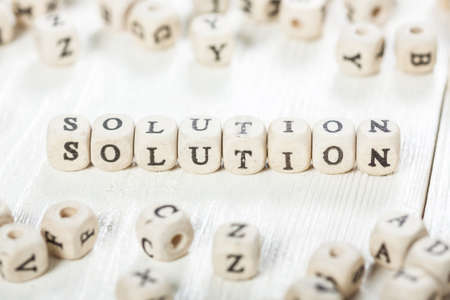 Word SOLUTION formed by wood alphabet blocks. On old wooden table.