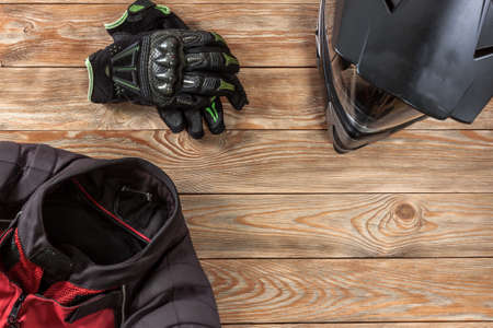 Overhead view of biker accessories placed on rustic wooden table. Items included motorcycle helmet, gloves and jacket. Motorcycle travel dream concept. Reklamní fotografie