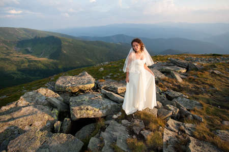 Bride in wedding dress at sunset in the mountains. Reklamní fotografie