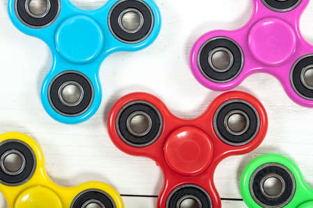 Group of fidget spinner stress relieving toy on a old wooden background. Reklamní fotografie