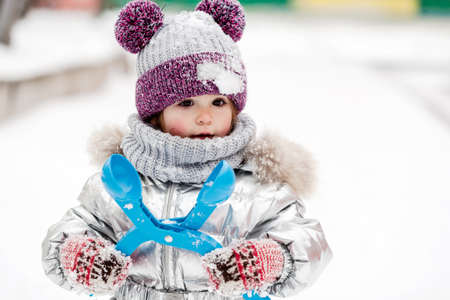 Little girl in silver jacket with scarf and pink hat in snowy park at winter. Reklamní fotografie