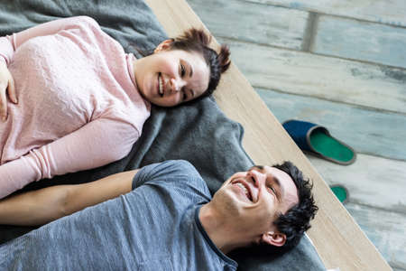 Romantic couple. Beautiful young loving couple embracing while lying on big cozy bed at home.