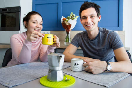 Romantic couple. Beautiful young loving couple having fun while drinking coffee at home.