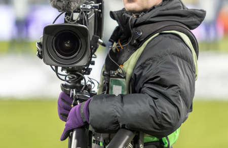 Hand Video camera operator camcorder working with his equipment outdoor on football match.
