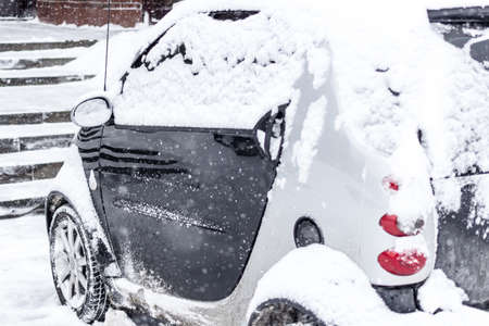 Car covered with snow after snowfall. Winter urban scene. Focus on front wheel. Reklamní fotografie