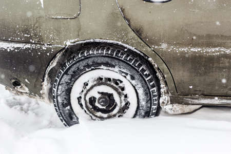Car covered with snow after snowfall. Winter urban scene. Tire close-up view.
