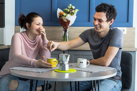 Romantic couple. Beautiful young loving couple relaxing and drinking coffee at home.