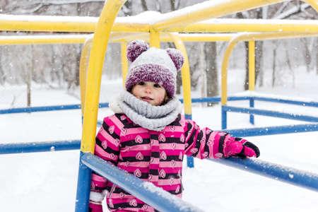 Little girl having fun outside at winter time.