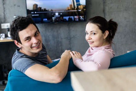 Romantic couple. Beautiful young loving couple embracing while sitting in big cozy sofa bed at home.