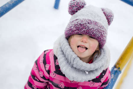Little girl having fun outside at winter time.