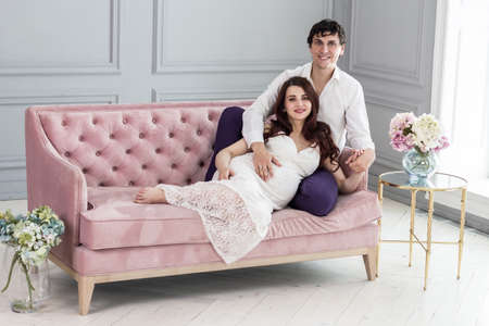 Pregnancy and people concept - happy man hugging his pregnant wife at home.